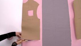 切开织品的裁缝 裁缝在工作 缝合从桃红色织品的一件运动衫 剪裁的衣裳,设计车间 股票录像