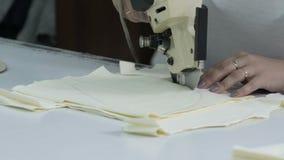 切开织品,缝合的工作 剪接室,切开剪裁刀子的轻的米黄布料 缝合的衣裳的样式 股票录像