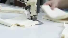 切开织品,缝合的工作 剪接室,切开剪裁刀子的轻的米黄布料 股票录像