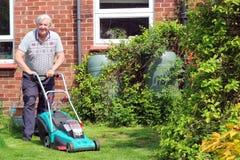 切开草坪的人。 库存图片