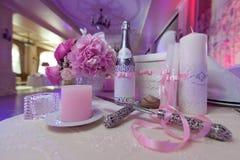 切开蛋糕的刀片和刀子 香宾、蜡烛和花当婚礼装饰 免版税库存照片