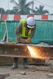 切开金属的建筑工人使用小型发焰装置在建造场所 免版税图库摄影