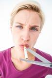切开香烟的美丽的金发碧眼的女人 免版税库存照片