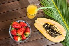 切成了两半成熟在高玻璃的番木瓜新鲜的草莓热带汁与秸杆 在板条木表上的棕榈叶在咖啡馆 库存照片