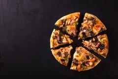 切成切片可口新鲜的薄饼用蘑菇和意大利辣味香肠在黑暗的背景 顶视图 在黑色的薄饼 库存照片