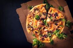 切成切片可口新鲜的薄饼用蘑菇和意大利辣味香肠在黑暗的背景 顶视图 在黑色的薄饼 图库摄影