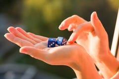 切成小方块在女性手,日落背景上 赌博的设备 库存图片