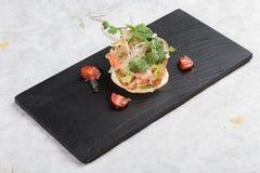 切成小方块的三文鱼沙拉用鲕梨、蕃茄、葱、辣椒和香菜在washi的黑长方形石头板材服务 库存图片