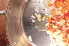 切成小方块的和切好的红萝卜、葱、大蒜和油sautee的 库存照片