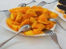 切成小方块的番木瓜在有叉子和匙子的一块板材说谎 图库摄影