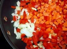 切成小方块的红辣椒、红萝卜和葱在一个非棍子长柄浅锅准备好烹调 库存图片