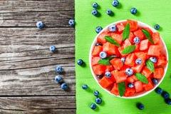 切成小方块的西瓜、蓝莓和新鲜薄荷沙拉在绿色 图库摄影