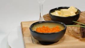切成小方块的黄油,鱼子酱,黑面包 碗与匙子的红色鱼子酱服务用切的面包、黄油和草本在白色 库存照片