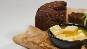 切成小方块的黄油,鱼子酱,黑面包 碗与匙子的红色鱼子酱服务用切的面包、黄油和草本在白色 图库摄影
