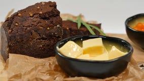 切成小方块的黄油,鱼子酱,黑面包 碗与匙子的红色鱼子酱服务用切的面包、黄油和草本在白色 免版税图库摄影