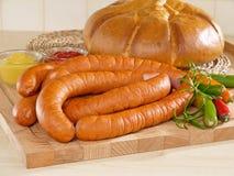 切新鲜的香肠的董事会面包 库存照片