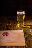 切板用在充分的杯的香肠啤酒附近 库存照片