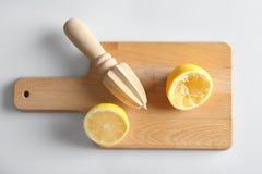 切板用被切的柠檬和木柑橘绞刀 免版税图库摄影