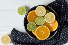切柠檬、桔子和石灰在蓝色陶瓷碗和逗人喜爱的t 免版税库存照片