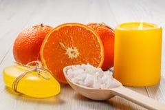 切桔子用两个整个桔子,肥皂,有白色的木匙子 库存照片