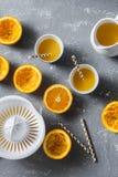 切桔子,新鲜的橙汁,在一张灰色桌上的手工柑橘榨汁器,顶视图 健康的食物 免版税库存图片