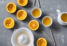 切桔子,新鲜的橙汁,在一张灰色桌上的手工柑橘榨汁器,顶视图 免版税库存照片