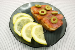 切片一条熏制的驼背三文鱼用橄榄和柠檬 免版税库存图片