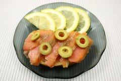切片一条熏制的驼背三文鱼用橄榄和柠檬 库存照片