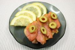 切片一条熏制的驼背三文鱼用橄榄和柠檬 图库摄影