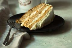 切片与乳脂干酪结霜的自创红萝卜和蜜糕在一块黑暗的板材、杯子coffe或茶,舒适心情 免版税库存照片