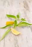 切片与叶子的新鲜的柠檬在木背景 免版税库存照片