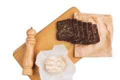 切片与向日葵种子的黑黑麦面包在一个木板说谎在乳酪旁边在刀子附近 库存照片