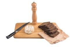 切片与向日葵种子的黑黑麦面包在一个木板说谎在乳酪旁边在刀子附近 免版税库存图片