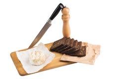 切片与向日葵种子的黑黑麦面包在一个木板说谎在乳酪旁边在刀子附近 免版税图库摄影