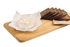 切片与向日葵种子的黑黑麦面包在一个木板说谎在乳酪旁边 免版税库存照片