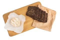 切片与向日葵种子的黑黑麦面包在一个木板说谎在乳酪旁边 免版税库存图片