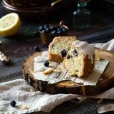 切片与白色釉的自创可口bundt蛋糕在木立场的上面 免版税库存照片