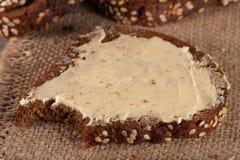 切片与芝麻籽和黄油的黑面包在老木背景 免版税库存图片