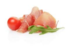 切片与芝麻菜叶子和蕃茄的意大利熏火腿 免版税库存图片