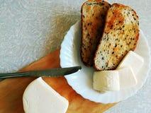 切片乳酪和炸面包在一块白色板材 免版税库存照片