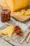 切片乳酪用蜜饯和核桃在玻璃板 库存图片