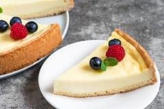 切片乳酪蛋糕用新鲜的莓果和薄菏在石背景 关闭 免版税库存照片