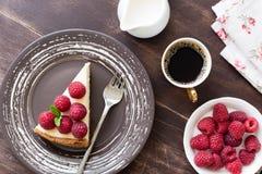 切片乳酪蛋糕用莓和咖啡在木桌上的 库存图片