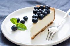 切片乳酪蛋糕用蓝莓和薄荷的叶子在白色板材 免版税库存照片