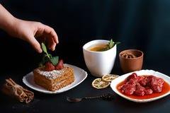 切片倾吐的蜜糕,厨师装饰用草莓,点心叉子,薄菏,烘干了柠檬,桂香,草莓酱棍子  库存照片