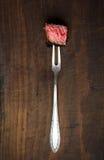切片半生半熟在肉的ribeye牛排在黑暗的木背景分叉 库存图片