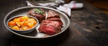 切片半生半熟烤肉牛排和辣调味汁在土气木背景调味 免版税库存照片