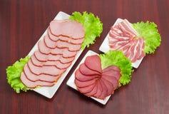 切片各种各样的准备的猪肉用在长方形盘的莴苣 库存照片