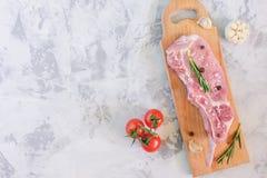 切片在一个木切板的未加工的猪肉 肉牛排用蕃茄、大蒜和迷迭香 在灰色石头的拷贝空间 库存照片