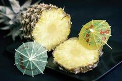 切片在一个黑色的盘子的成熟菠萝有鸡尾酒,在黑暗的背景的伞的装饰的 免版税库存照片